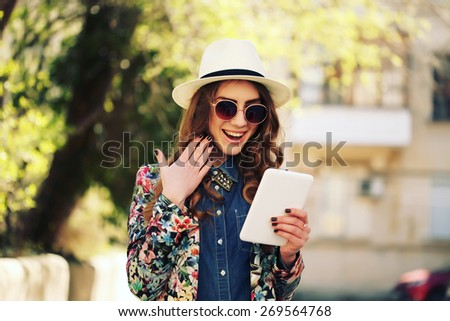 Beautiful smiling hipster woman wear vintage sunglasses, jeans shirt, white hat and jacket take a picture of herself with digital tablet. Selfie style. Toned in warm colors. Outdoors shot, lifestyle - stock photo