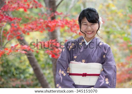 Beautiful smiling Japanese girl in a seasonal kimono in a traditional Japanese garden during autumn - stock photo