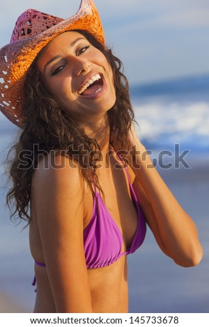 Beautiful smiling laughing happy young mixed race sexy Hispanic woman in bikini and cowboy hat on a tropical beach  - stock photo