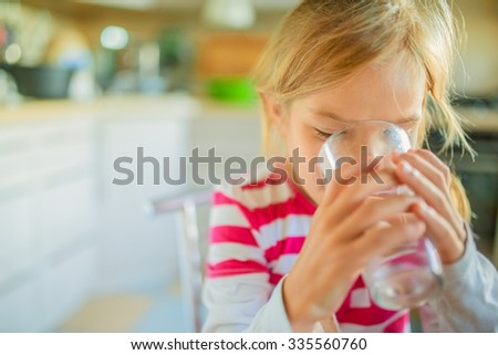 Beautiful smiling little girl drinking a glass of water against the background of the kitchen. - stock photo