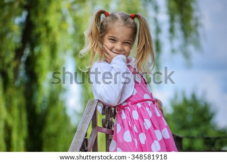 Beautiful smiling little girl in a pink dress standing near the fence.