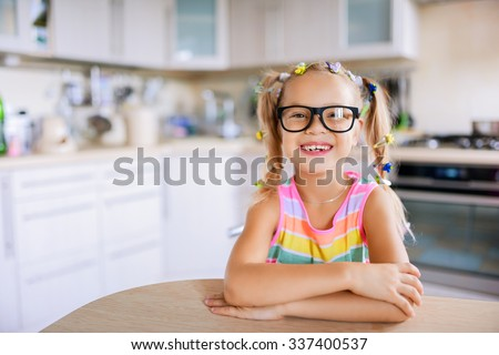 Beautiful smiling little girl in glasses sits at a table in the kitchen.