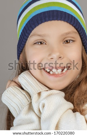 Beautiful smiling little girl in knitted cap, on gray background.