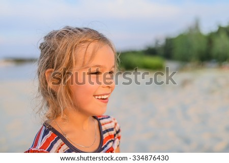 Beautiful smiling little girl on a background of a sandy beach. - stock photo