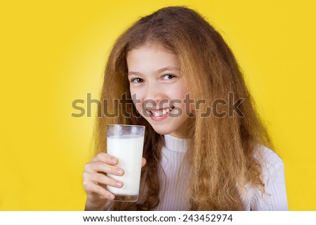 Beautiful smiling little girl with curly hair holding glass of milk enjoying it, over yellow background.Health,Drink,Enjoyment - stock photo