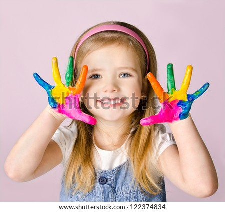 Beautiful smiling little girl with hands in the paint - stock photo