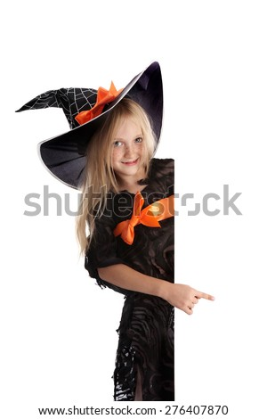 Beautiful Smiling Little Girl with Long Blonde Hair in the Witch Costume Pointing the Sign . Black witch hat with web, spider and orange bow. - stock photo