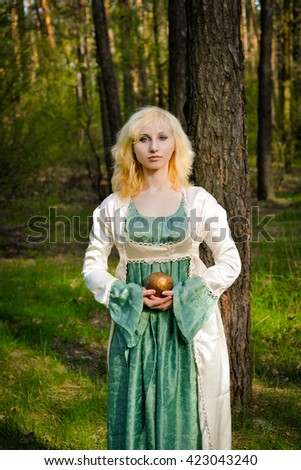 Beautiful smiling magic girl in the wood. Fashionable shooting of a young short haired blond woman posing in the forest park wearing fancy empire style dress. Concept of fantasy and magic.
