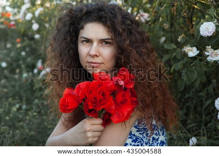 Beautiful smiling mature girl with curly hair in poppies field at sunset. outdoor portrait. Young sensual girl in poppies field