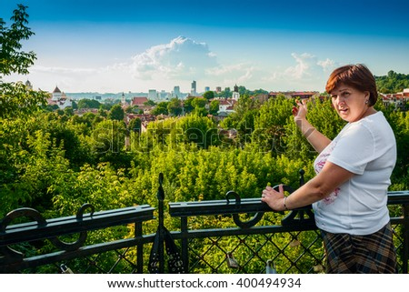 Beautiful smiling middle-aged woman with city view on background  - stock photo