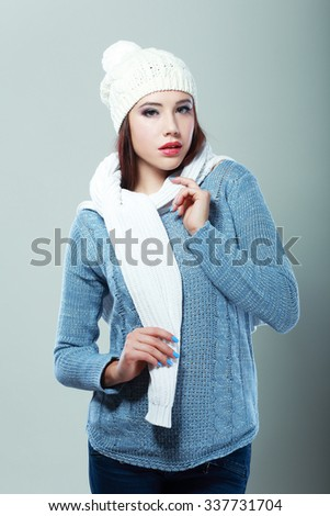 beautiful smiling mixed rase caucasian/asian female model wearing a blue woolen sweater - stock photo