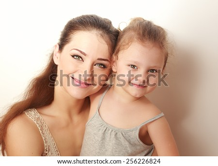 Beautiful smiling mother and small happy daughter cuddling. Closeup portrait - stock photo