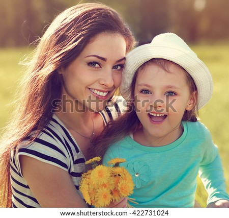 Beautiful smiling mother embracing her cute daughter with yellow bright flowers on summer background. Closeup portrait - stock photo