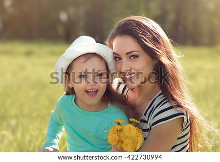 Beautiful smiling mother embracing her cute daughter with yellow bright flowers on summer background