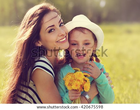 Beautiful smiling mother embracing her daughter with yellow bright flowers on summer background. Closeup portrait of family love in mother day - stock photo