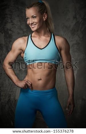 Beautiful smiling muscular bodybuilder woman - stock photo