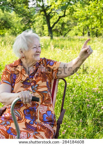 Beautiful smiling old woman pointing on natural background - stock photo