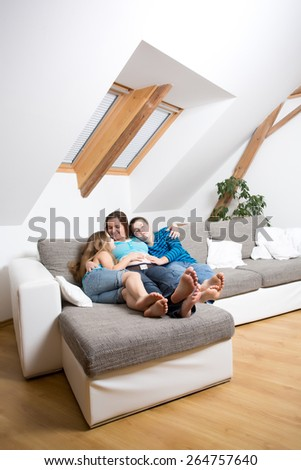 Beautiful smiling pregnant mother with her children at the living room