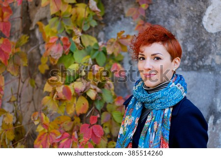 Beautiful smiling red-haired woman portrait with short hair on autumn leaves background. Young girl outdoors portrait. Soft sunny colors.