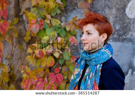 Beautiful smiling red-haired woman portrait with short hair on autumn leaves background. Young girl outdoors portrait. Side view. Soft sunny colors.