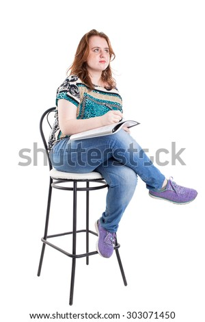 Beautiful smiling redhead plus size wreckled model with folder and ballpoint pen sitting on the bar chair. Isolated on a white background.