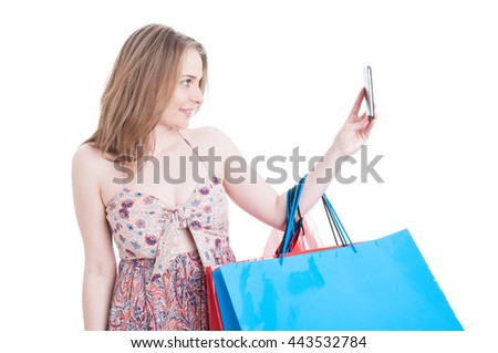Beautiful smiling shopper with gift bags taking a selfie with modern cellphone isolated on white background