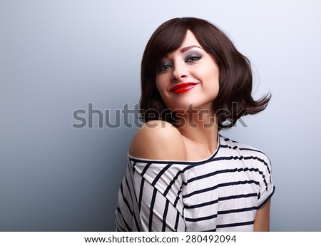 Beautiful smiling short hair woman looking happy on blue background. CLoseup portrait - stock photo