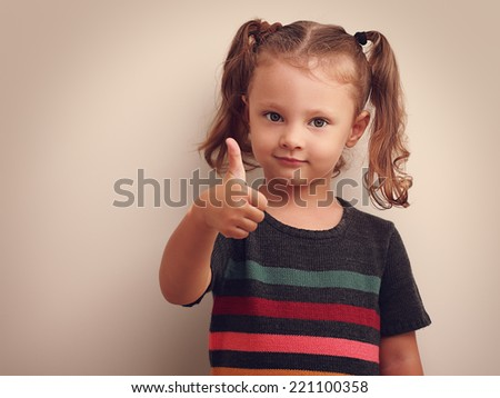 Beautiful smiling small kid girl showing thumb up. Vintage portrait - stock photo