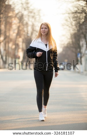 Beautiful smiling sporty girl in earphones walking in the morning street
