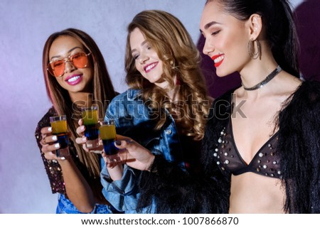 beautiful smiling stylish multiethnic girls holding glasses with cocktails at party