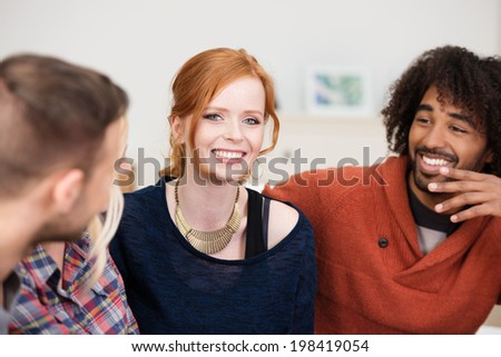 Beautiful smiling stylish redhead woman sitting on a sofa with two male friends, one a young African American, focus to the woman - stock photo