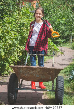Beautiful smiling teen girl in wellies working in garden