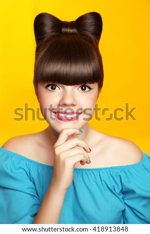 Beautiful smiling teen girl with bow hairstyle, makeup and colourful manicured polish nails. Funny girl in blue dress showing manicure fingers isolated on studio yellow background. - stock photo