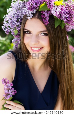 Beautiful smiling teen girl with fashion makeup is wearing beautiful wreath of lilac flowers - stock photo