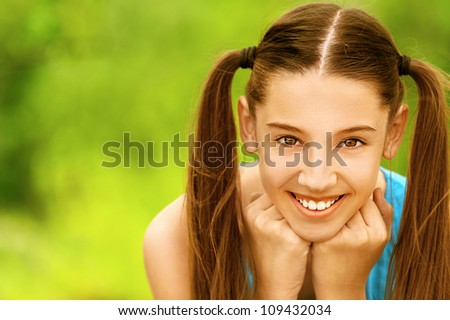 Beautiful smiling teenage girl, against green of summer park. - stock photo