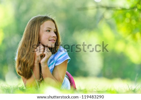 Beautiful smiling teenage girl in blue blouse lying on grass, against green of summer park. - stock photo