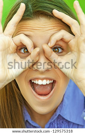 Beautiful smiling teenage girl in blue shirt shows glasses out of fingers, against background of summer green park. - stock photo
