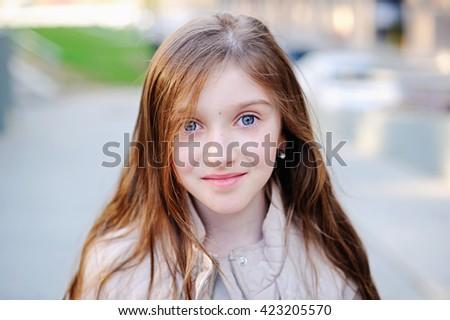 Beautiful smiling teenage girl in the city - stock photo