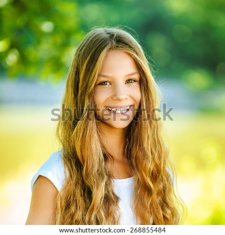 Beautiful smiling teenage girl in white blouse, against of summer park. - stock photo