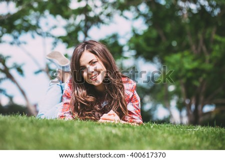 Beautiful smiling teenage girl  lying on the grass in the park looking at the camera - stock photo