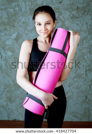 beautiful smiling teenage girl wearing sports clothes with a yoga mat  - stock photo