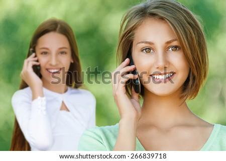 Beautiful smiling teenage girlstalking on mobile phone, against background of summer green park. - stock photo