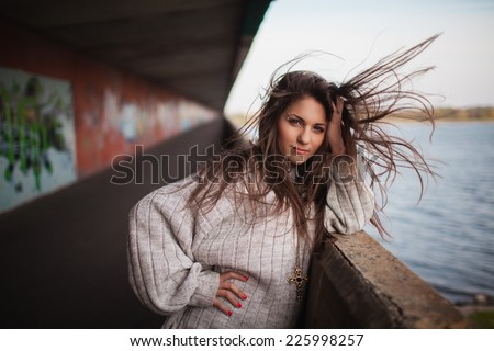 beautiful smiling teenager girl with long hair flying in the wind and make up