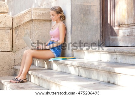 Beautiful smiling teenager student girl sitting on stone steps of college building entrance using a laptop computer, doing homework, school outdoors. Adolescent pupil technology lifestyle, exterior.