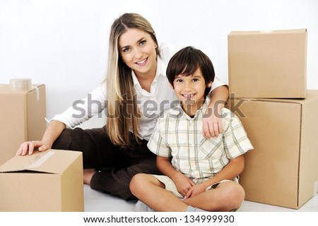 Beautiful smiling woman and little boy openig cardboard box - stock photo