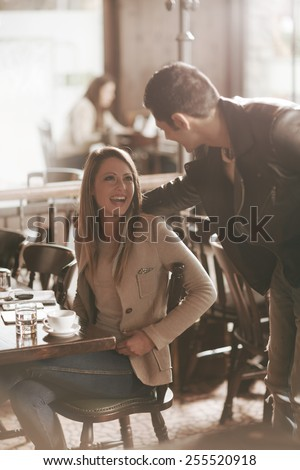 Beautiful smiling woman and stylish man meeting at the bar, he is touching her back - stock photo