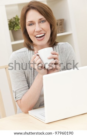 Beautiful, smiling, woman at home at a table using her laptop computer drinking a mug of tea or coffee - stock photo