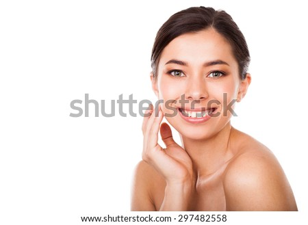 Beautiful smiling woman cares for the face - stock photo