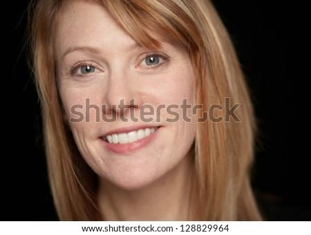 Beautiful smiling woman closeup on black background - stock photo