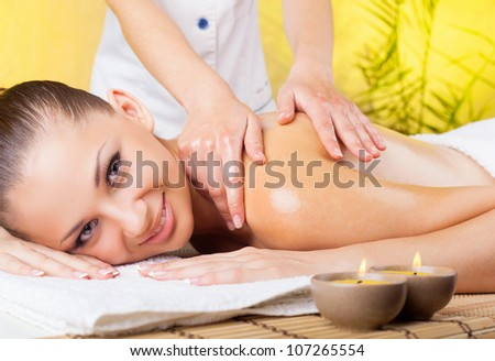 Beautiful smiling woman getting a massage in the spa salon - stock photo